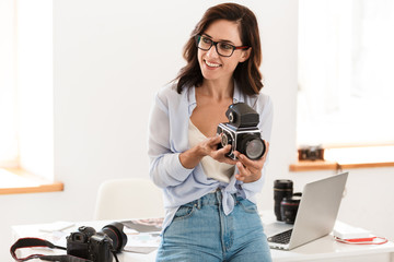 Beautiful young woman photographer working at her office