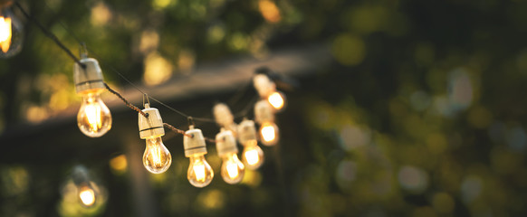 Obraz outdoor party string lights hanging in backyard on green bokeh background with copy space - fototapety do salonu