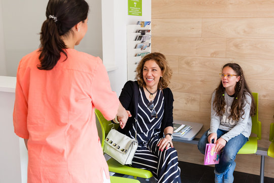Female doctor welcoming patients in the waiting room of a medical clinic, shaking hands