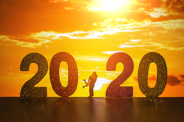 silhouette of miniature couple with text 2020  over blurred sunset background image for Happy new year 2020 or love family concept.