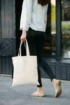 Woman holding white textile eco bag against urban city background. . Ecology or environment protection concept. White eco bag for mock up.