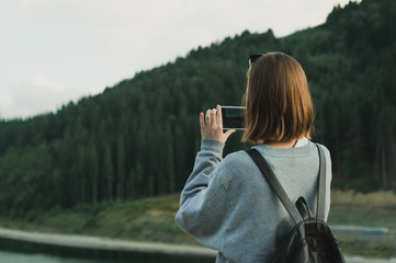 Young female traveler in grey sweatshirt taking photo on smartphone of mountain forest landscape. Back view of tourist woman using cellphone to photograph coniferous woods. Travel, vacation concept.