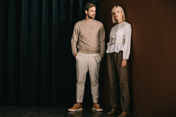 full length view of stylish man with hands in pockets and blonde woman in blouse standing near curtain Wall mural