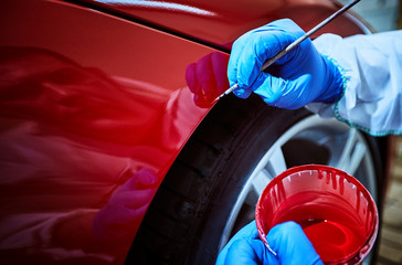 Tinting defects of a red car paint on the service