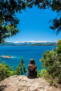 Young woman sitting on the rock and watching at Nahuel Huapi lake, San Carlos de Bariloche Argentina. Waves on the lake. Mountains with fresh snow surrounding the lake.