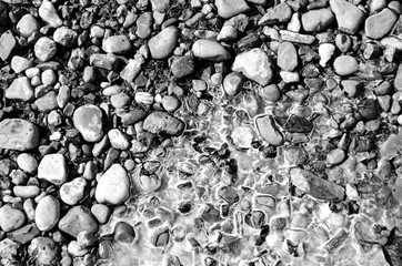 Stones on the river bank with ice in the spring. Stone coast and ice