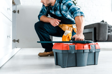 cropped view of bearded handyman sitting and holding toolbox