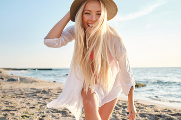 Obraz Young joyful blond woman in swimsuit and white shirt wearing hat while happily looking in camera with sea on background - fototapety do salonu