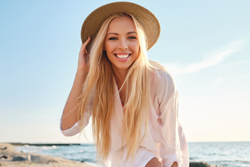 Young attractive smiling blond woman in shirt and hat joyfully looking in camera with sea on background