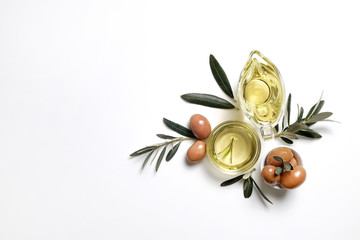 Bunch of local produce Turkish green gemlik olives with glass cup & gravy boat full of extra virgin golden oil, olea europaea tree leaves. Close up, top view, copy space, isolated white background.