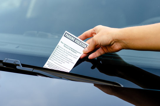 Close-up Of A Woman Taking Parking Ticket On Car's Windshield