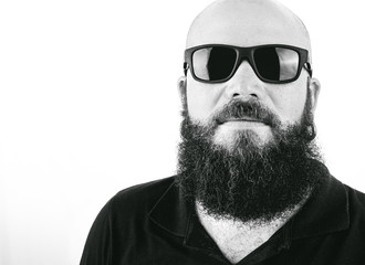 Photograph of a hipster style man wearing sunglasses in studio with white background.