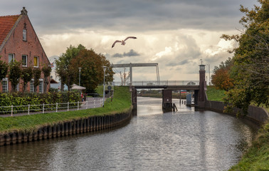 A canal with a drawbridge in the city Carolinensiel in northern Germany. A farmhouse can be seen and street lamps. Cloudy colorful sky in the late afternoon.