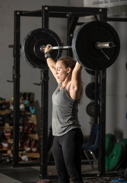 Strong young woman lifting heavy weights over her head