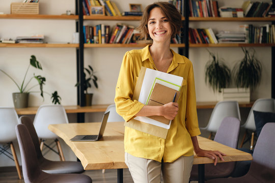 Young cheerful woman in yellow shirt leaning on desk with notepad and papers in hand while joyfully looking in camera in modern office