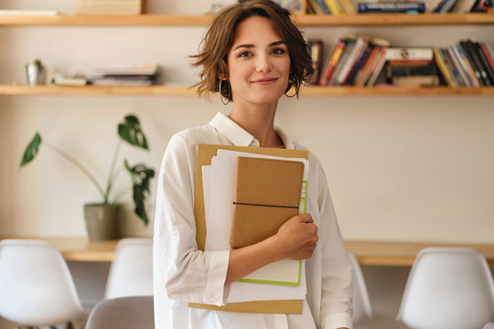 Young beautiful smiling woman dreamily looking in camera with papers and notepad in office