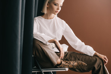 stylish blonde woman in white blouse sitting on chair near curtain on brown Wall mural