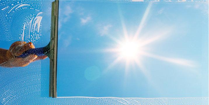 Fensterputzer putzt Fenster mit Schaum und Abzieher im Sonnenlicht - Panorama