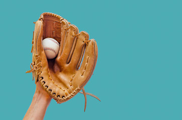 Hand in a leather baseball glove caught a ball on a green background