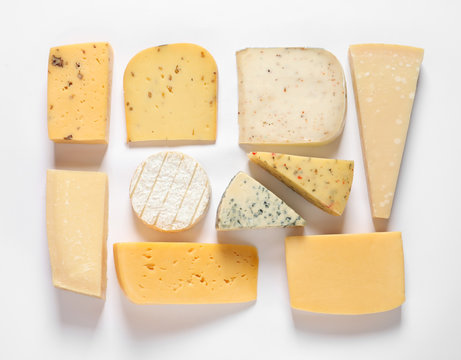 Composition with different kinds of tasty cheese on white background, top view