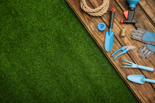 Wooden surface with gardening tools on green grass, flat lay. Space for text