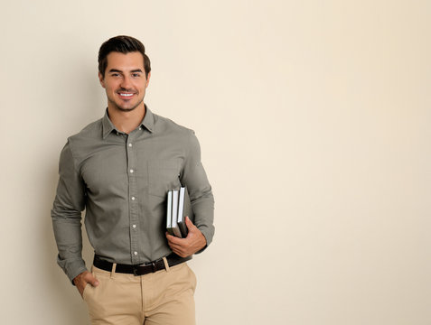 Young male teacher with books on beige background. Space for text