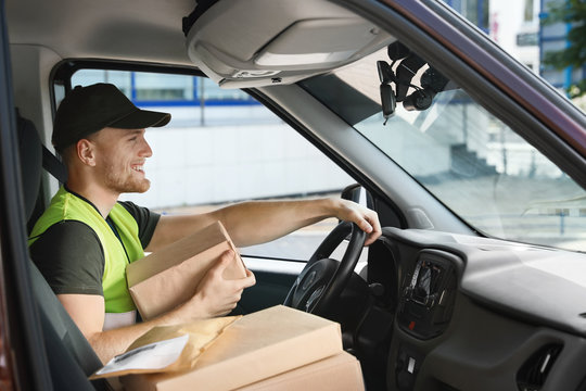 Young courier with parcels in delivery car