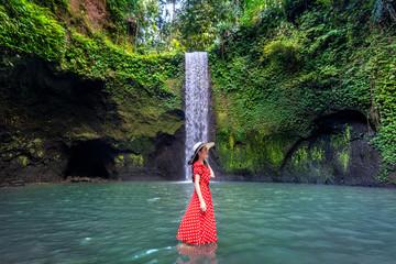 Canvas Print - Beautiful girl standing in Tibumana waterfall in Bali, Indonesia.
