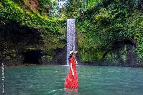 Wall mural Beautiful girl standing in Tibumana waterfall in Bali, Indonesia.