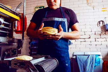 Cut in view of man collecting wheat tortillas from baking machine
