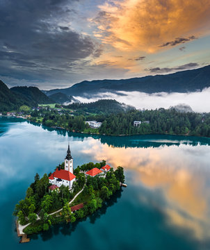 Bled, Slovenia - Beautiful aerial view of Lake Bled (Blejsko Jezero) with the Pilgrimage Church of the Assumption of Maria on a small island and dramatic reflecting clouds and sky at summer time