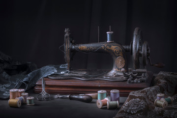 The sewing machine and accessories - threads, needle, scissors, measuring tape.