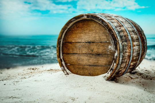 Old wooden barrel on the sandy beach with dark blue ocean view.