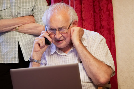 Old elderly senior man on phone at laptop computer at risk to cyber attack and online bank fraud