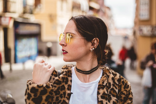 Stylish portrait of young woman looking aside wearing yellow sunglasses, trendy animal, leopard print faux fur coat, fashion sunglasses, in the street of European city