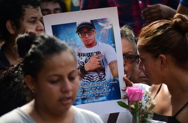 "Relatives and friends carry a poster with a picture of Erick Hernandez Enriquez, who died after an arson attack by suspected gang members at ""El Caballo Blanco"" bar, during his funeral at the Panteon cemetery in the southern Mexican port of Coatzacoalcos"