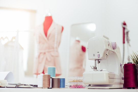 Closeup of sewing machine with fashion designer showroom studio workshop background with new collection of pink pastel female clothes design. Tailor and sewing concept. Dressmaker modern room interior
