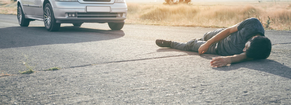 Caucasian injured man lying on asphalt.