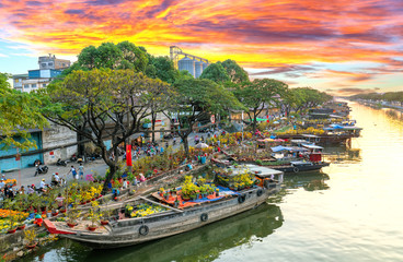 Ho Chi Minh City, Vietnam - February 3rd, 2019: Sunset boat dock flower market along canal wharf. This is place farmers sell apricot and other flowers on Lunar New Year in Ho Chi Minh city, Vietnam