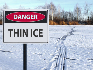 sign danger thin ice and footprints road on snow and ice