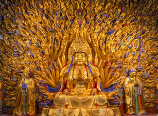 Golden sculpture of Avalokiteshvara Buddha or Guanyin with thousand hands at Dazu Rock Carvings at Mount Baoding or Baodingshan in Dazu, Chongqing, China. UNESCO World Heritage Site.