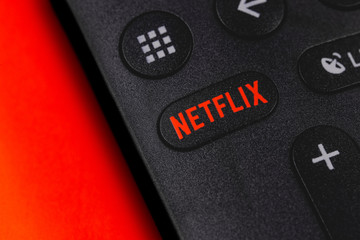 Netflix button on the remote controller on red background. Netflix is an international leading subscription service for watching TV episodes and movies. Moscow, Russia - April 19, 2019
