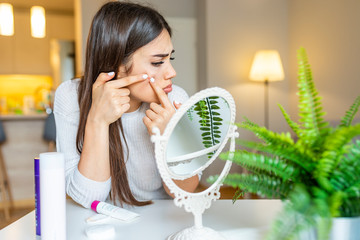 Portrait of beautiful young woman squeezing pimples while looking at the mirror. Pimple on cheek. Young woman squeeze her acne in front of the mirror. I'm sure this will go away if I pop it.