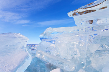 Winter landscape of the frozen lake Baikal. Fields of ice hummocks with transparent ice blocks on the Small Sea Strait against a blue sky. Cold natural background