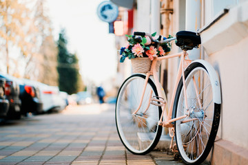 Photo sur Plexiglas Velo White bicycle with basket of flowers standing near the door on the street in city.