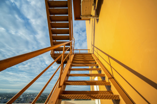 Fire escape stairs mounted to the outside, Emergency exit with yellow wall..