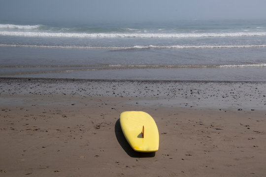 A yellow surfboard sitting on the sand