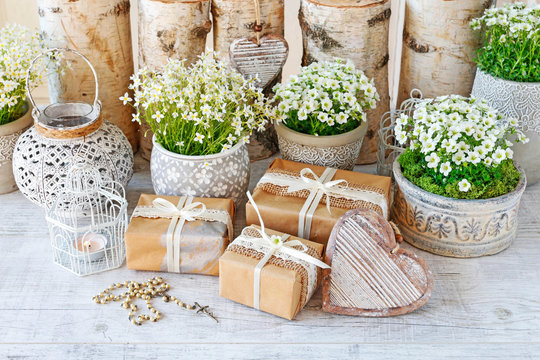 Beautifully wrapped gifts and flowers in the background