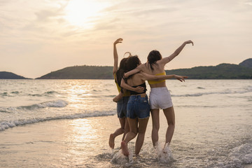 Group of three Asian young women running on beach, friends happy relax having fun playing on beach near sea when sunset in evening. Lifestyle friends travel holiday vacation on beach summer concept.