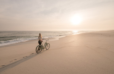 Beautiful blonde woman and bicycle traveling down a quiet beach at sunset.
